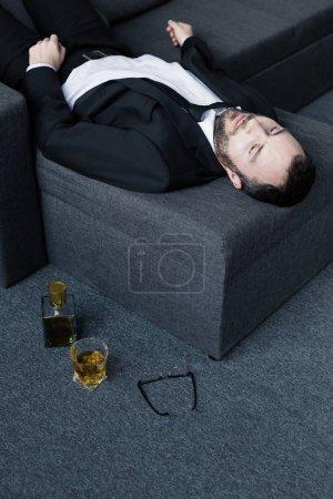 Foto de Vista de ángulo alto de empresario molesto acostado en el sofá cerca de vasos, botella y vaso de whisky en el suelo - Imagen libre de derechos