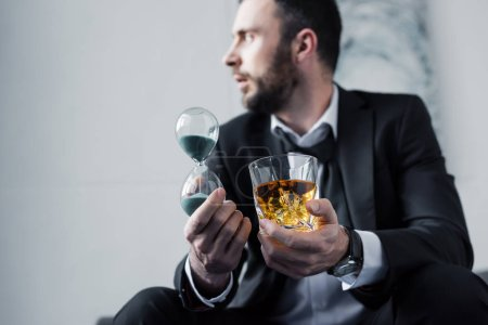 Photo for Selective focus of frustrated businessman holding glass of whiskey and hourglass - Royalty Free Image