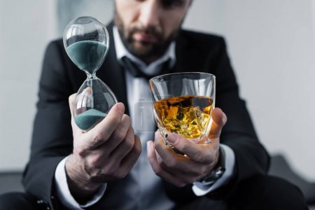 Photo for Cropped view of depressed businessman holding hourglass and glass of whiskey - Royalty Free Image