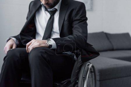 Photo pour Vue recadrée de l'homme handicapé dans le procès noir s'asseyant dans le fauteuil roulant avec la tête courbée - image libre de droit