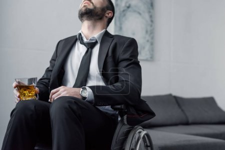 Photo for Cropped view of depressed disabled man in suit sitting in wheelchair with glass of whiskey - Royalty Free Image