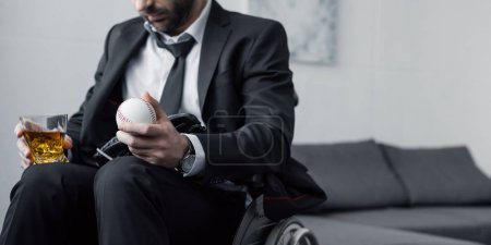 Photo for Panoramic shot of disabled man in wheelchair holding ball and glass of whiskey - Royalty Free Image