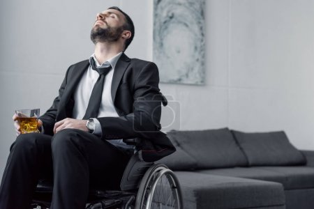 Photo for Upset bearded disabled man sitting in wheelchair with closed eyes and holding glass of whiskey - Royalty Free Image