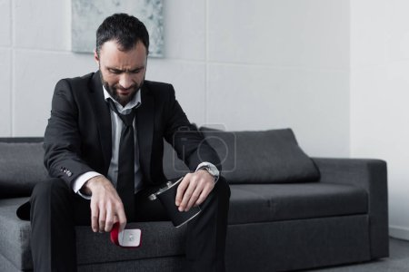 Photo for Depressed bearded man sitting on sofa while holding gift box and flask - Royalty Free Image