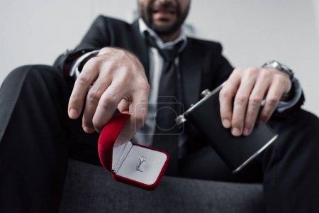 Photo pour Vue partielle de l'homme déprimé tenant boîte cadeau avec anneau et fiole - image libre de droit