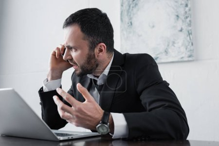 Photo for Angry businessman quarreling while sitting at workplace and talking on smartphone - Royalty Free Image