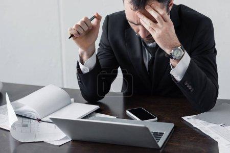Foto de Pensativo hombre de negocios sentado en el lugar de trabajo cerca de la computadora portátil, documentos y teléfono inteligente con pantalla en blanco - Imagen libre de derechos
