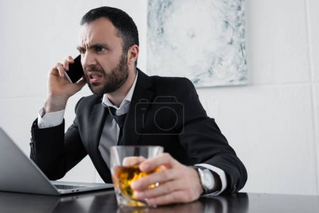 Photo for Selective focus of angry businessman quarreling while talking on smartphone and holding glass of whiskey - Royalty Free Image