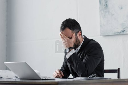 Photo for Upset businessman holding hand on face while sitting at workplace - Royalty Free Image