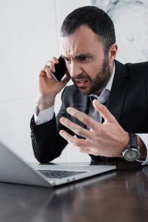 Photo for Angry businessman quarreling while talking on smartphone near laptop - Royalty Free Image