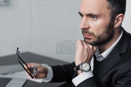 Foto de Upset bearded businessman sitting at workplace, holding glasses and looking away - Imagen libre de derechos