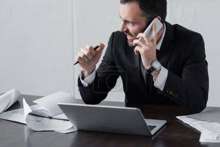 Photo for Displeased businessman in black suit talking on smartphone while sitting at workplace - Royalty Free Image