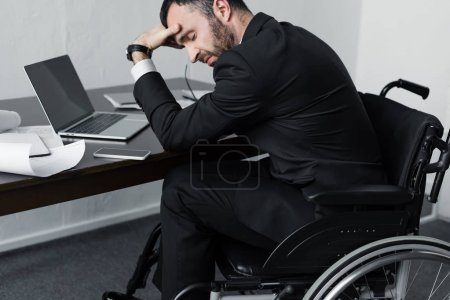 Photo for Depressed disabled businessman in wheelchair sitting at workplace with laptop, smartphone and papers - Royalty Free Image