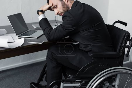 Photo for Upset disabled businessman sitting at workplace in wheelchair and holding hand on forehead - Royalty Free Image