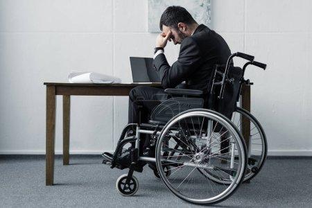 Photo pour Homme d'affaires handicapé déprimé s'asseyant dans le fauteuil roulant au lieu de travail avec la tête courbée - image libre de droit