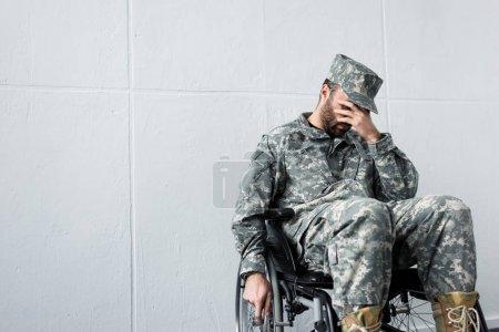 Photo pour Homme militaire handicapé déprimé dans l'uniforme s'asseyant dans le fauteuil roulant et retenant la main sur le visage - image libre de droit