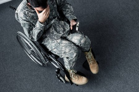 Photo for Overhead view of disabled military man in uniform sitting with flask in wheelchair and covering face with hand - Royalty Free Image