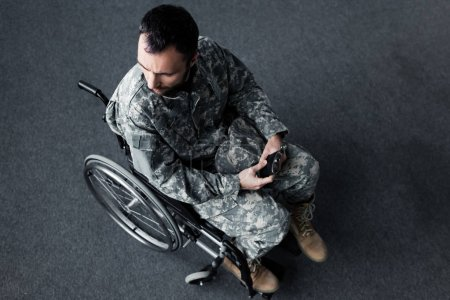 Photo for Overhead view of disabled man in uniform sitting in wheelchair and holding cap in hands - Royalty Free Image