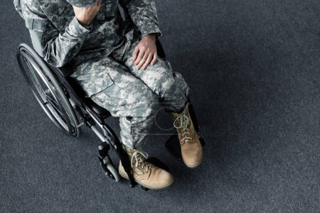 Photo for Overhead view of depressed disabled man in military uniform sitting in wheelchair - Royalty Free Image