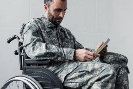 Foto de Pensativo discapacitado hombre sin afeitar en uniforme militar sentado en silla de ruedas y mirando la foto en el marco - Imagen libre de derechos