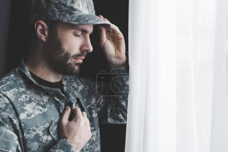 Photo for Pensive bearded man in uniform holding hand on chest while standing by window with closed eyes - Royalty Free Image