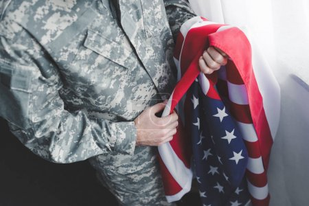 cropped view of adult man in military uniform holding usa national flag