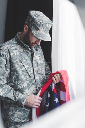 Photo pour Foyer sélectif de l'homme militaire triste dans le drapeau national d'usa de fixation uniforme tout en restant par la fenêtre avec la tête courbée - image libre de droit