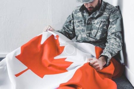 Photo pour Homme déprimé dans l'uniforme militaire s'asseyant sur l'étage dans le coin et retenant le drapeau national de canada - image libre de droit