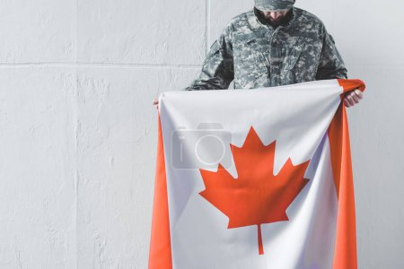 Photo for Man in military uniform holding canada national flag while standing near white wall with bowed head - Royalty Free Image