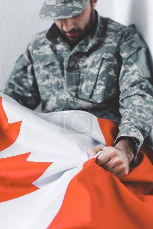 Photo pour Foyer sélectif de l'homme déprimé dans l'uniforme militaire s'asseyant dans le coin et retenant le drapeau national de canada - image libre de droit