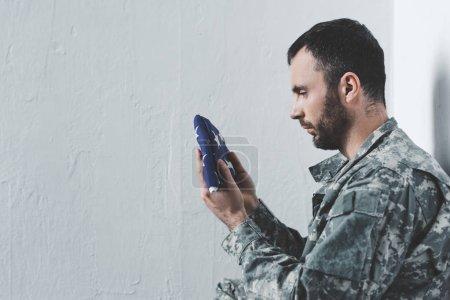 Photo pour Vue latérale de l'homme barbu dans l'uniforme militaire se reposant par le mur blanc et retenant le drapeau national d'usa - image libre de droit