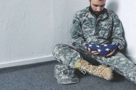 Photo for Sad bearded man in military uniform sitting on floor in corner and holding usa national flag - Royalty Free Image