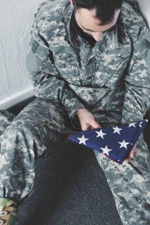 Photo pour Vue d'angle élevé de l'homme déprimé dans l'uniforme militaire s'asseyant sur l'étage dans le coin et retenant le drapeau national d'usa - image libre de droit