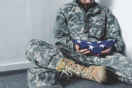 Photo pour Vue partielle de l'homme déprimé en uniforme militaire assis sur le sol gris dans un coin et tenant le drapeau national des Etats-Unis - image libre de droit