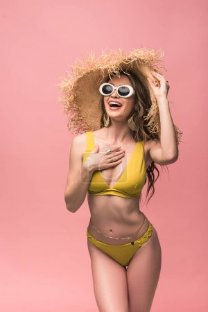 Photo for Charming girl in straw hat and sunglasses smiling isolated on pink - Royalty Free Image