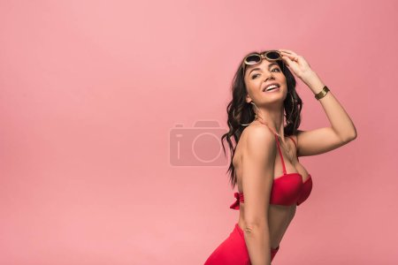 Photo for Smiling attractive woman in swimsuit and sunglasses isolated on pink - Royalty Free Image