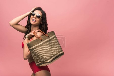 Photo for Smiling attractive woman in swimsuit and sunglasses holding beach bag isolated on pink - Royalty Free Image