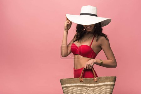 Photo for Smiling attractive woman in swimsuit and hat holding beach bag isolated on pink - Royalty Free Image