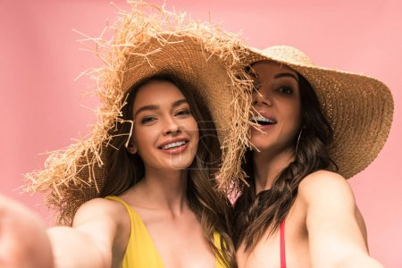 Photo for Two smiling girls in straw hats taking selfie isolated on pink - Royalty Free Image