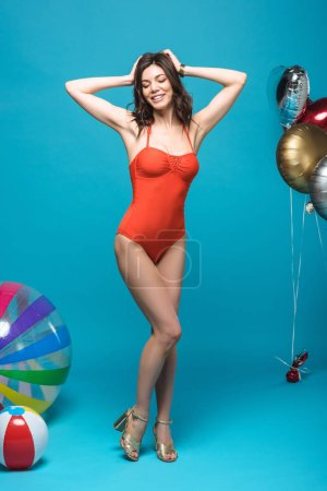 Photo for Full length view of shapely girl in swimsuit with balloons and inflatable beach balls smiling on blue - Royalty Free Image