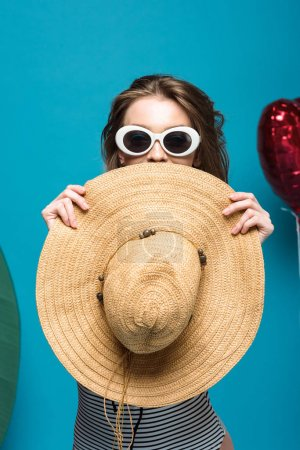 Photo pour Happy young woman in sunglasses holding straw hat on blue - image libre de droit