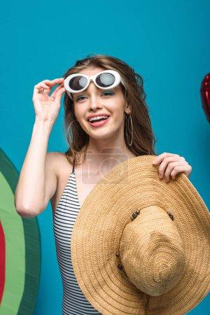 Foto de Mujer joven feliz en gafas de sol sosteniendo sombrero de paja en azul - Imagen libre de derechos