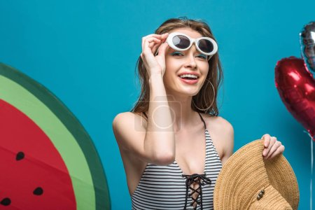 Photo pour Fille de sourire dans le maillot de bain et les lunettes de soleil retenant le chapeau de paille sur le bleu - image libre de droit