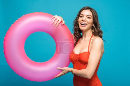 Photo for Pretty girl in swimsuit holding inflatable swim ring isolated on blue - Royalty Free Image