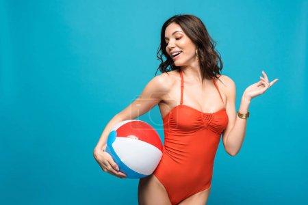 Photo pour Femme en maillot de bain tenant ballon de plage gonflable isolé sur bleu - image libre de droit