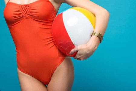 Photo pour Cropped view of woman in swimsuit holding inflatable beach ball isolated on blue - image libre de droit
