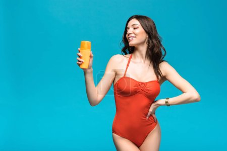 Photo for Pretty woman in swimsuit holding sunscreen isolated on blue - Royalty Free Image