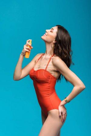 Photo pour Jolie femme en maillot de bain appliquant un écran solaire isolé sur le bleu - image libre de droit