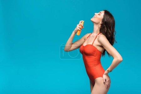Photo pour Fille de sourire dans le maillot de bain appliquant la protection solaire d'isolement sur le bleu - image libre de droit