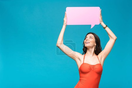 Photo for Charming girl in swimsuit holding speech bubble isolated on blue - Royalty Free Image